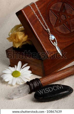 close up of wiccan objects - tarot cards box wand goddess pendant wisdom stone