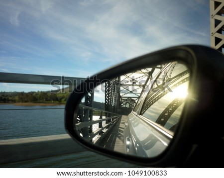 Close up of wind mirror with reflection of car running on a steel truss bridge over a lake. Bethanga Bridge, New South Wales, Australia. #1049100833