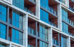 Close up of windows and balconies of a modern multi dwelling building of strata title living scheme.