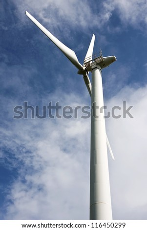Close up of Windturbine producing alternative energy with a blue sky