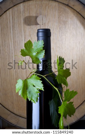 close-up of wine bottle with grape leaf.