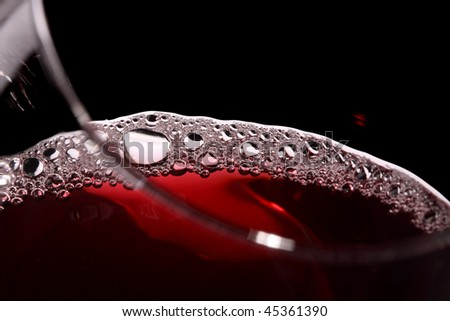 close up of wine in a glass isolated on black