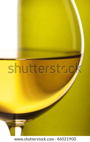 Close-up of wineglass with white wine and bottle in back light on white background.