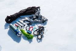Close-up of winter climbing equipment on fresh snow on a sunny day. Carbines with a rope gazebo and zhumar as well as other adaptations when practicing winter mountaineering