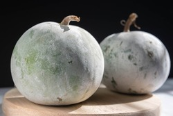 Close up of winter melon also called ash gourd,white gourd, winter gourd, tallow gourd, kundur and Chinese preserving melon on chopping board.