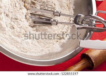 Close-up of wire whisk in flour with rolling pin on side