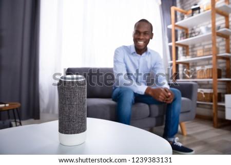 Close-up Of Wireless Speaker On Furniture Near Man Sitting On Sofa #1239383131