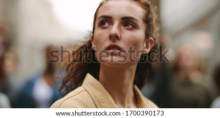 Close-up of woman activist looking away with group of protestors in background. Female activist demonstrating in the city. Stockfoto ©