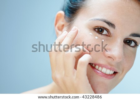 close up of woman applying eye cream