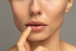Close up of woman applying moisturizing nourishing balm or ointment to her lips with her finger to prevent dryness and chapping in the cold season. Lip protection.