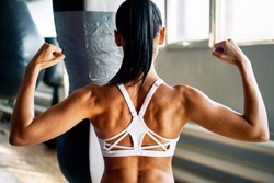 Close up of woman back with flexing her muscles in sweat on skin after workout. Female bodybuilder with perfect biceps