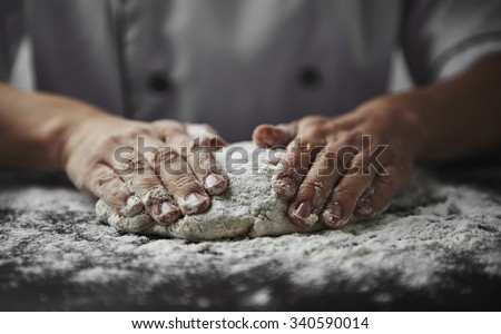 Close-up of woman baker hands kneading the dough on black board with flour powder. Concept of baking and patisserie.