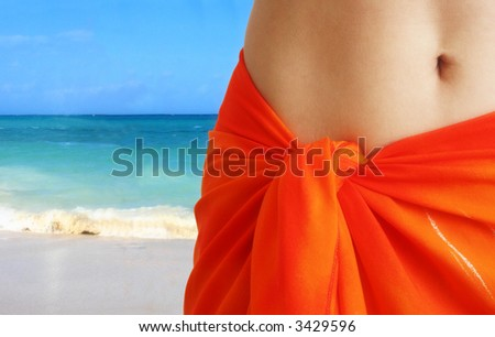 Close-up of woman belly in orange skirt on beach