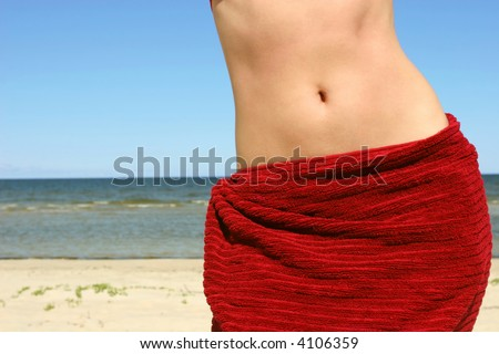 Close-up of woman belly on beach