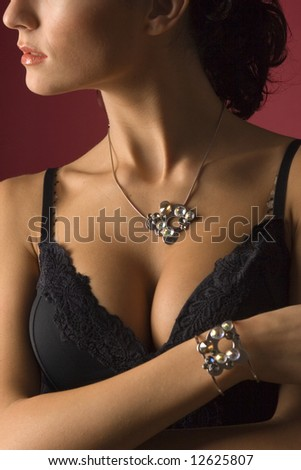 Close-up of woman body, studio shot isolated on red - stock photo
