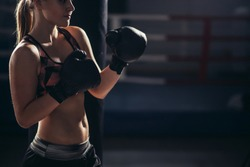 close up of woman boxer wearing gloves standing in boxing studio