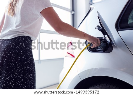 Close Up Of Woman Charging Electric Vehicle With Cable In Garage At Home Stockfoto ©