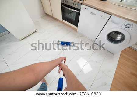 Close-up Of Woman Cleaning Kitchen Floor With Mop