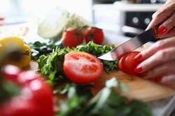 Close-up of woman cutting small tomato with knife. Process of preparing quick lunch. Fresh mellow vegetables on cutting board. Healthy and delicious eating concept