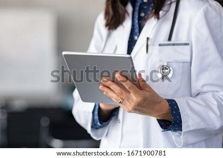 Close up of woman doctor hands using digital tablet at clinic. Closeup of doctor in labcoat and stethoscope holding digital tablet, reading patient report. Hands holding medical report, copy space.
