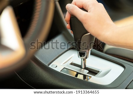 Close up of woman driver holding her hand on automatic gear shift stick driving as car. Stock photo ©
