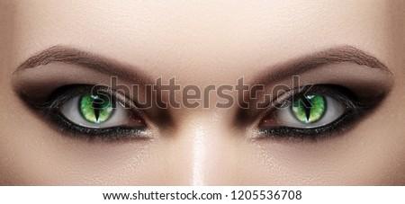Close-up of Woman Eyes. Halloween Makeup. Cat Eye Lens. Fashion Catwalk Black Make-Up. Luminous Green Cats Eyes. Closeup Shot