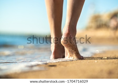 Close up of woman feet walking barefoot on sand beach in sea water. Vacation, travel and freedom concept. People relaxing in summer. Stockfoto ©