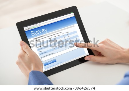 Close-up Of Woman Filling Online Survey Form On Digital Tablet #396426574