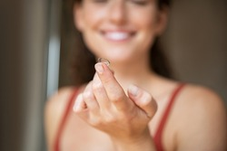 Close up of woman finger holding contact lens in front of her face.. Smiling young woman holding new contact lens on finger tip. Smiling girl holding contact lens, eyesight and eyecare concept.