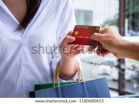 Close-up of woman giving a credit card to shopping.