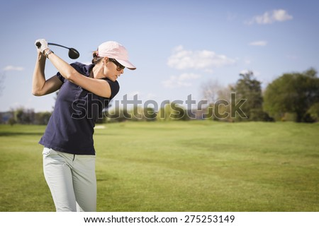 Close up of woman golf player swinging golf club, with empty copyspace.