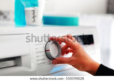 Close up of woman hand adjusting washing machine