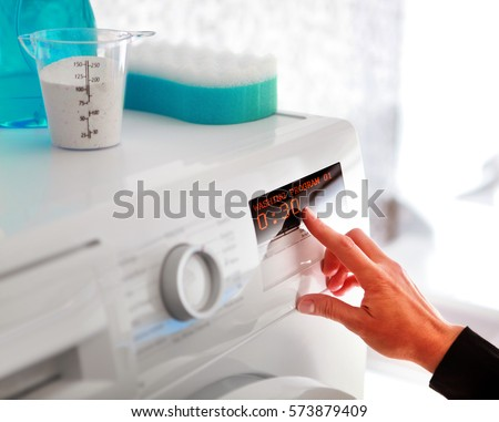 Close up of woman hand choosing program for washing machine