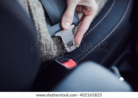 Close-up of woman hand fastening a seat belt in the car