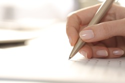 Close up of woman hand filling out form with pen on a desk