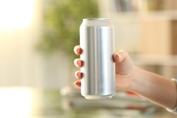 Close up of woman hand holding a soda drink can at home