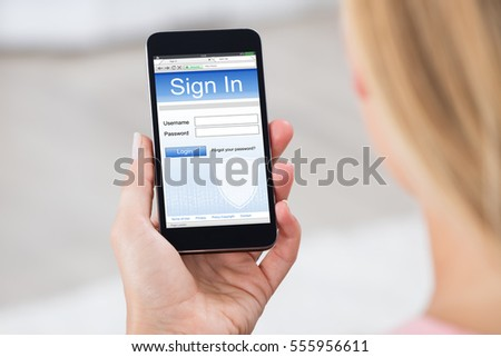 Close-up Of Woman Hand Holding Mobile Phone Showing Log In Page #555956611