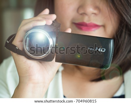 Close up of woman hand holding video camera or camcorder recording or taking events or medias with happy face in a working place with lens flare