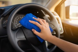Close-Up of Woman Hand is Cleaning Car Steering Wheel With Cleaner Microfiber Cloth, Car Washing and Vehicle Maintenance Service. Business Cars Wash and Transportation Automotive Equipment