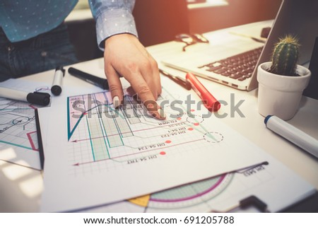 Close up of woman hand pointing at the graph. Female business analyst examining corporate income statistics. Sales increase dynamics research.  #691205788