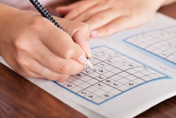 Close-up Of Woman Hand Solving Sudoku With Pen
