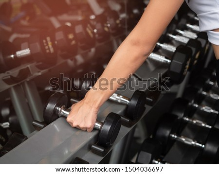 Close-up of woman hand takes a dumbbell in the gym. Closeup of dumbbells, strength training equipment.