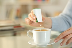 Close up of woman hand throwing saccharin pills on coffee cup on a desk at home