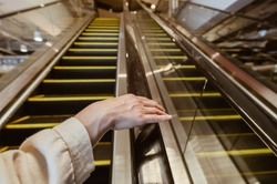 Close up of woman hand touching escalator handrail while using escalator in shopping mall for moving to another floor. Cocneptual of woman when visit shopping mall.