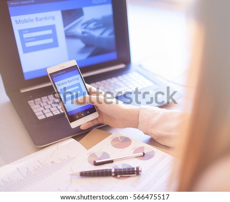 Close up of woman hand using on line banking on mobile phone logging in to a bank account typing password. Business, financial and secure payment concept. #566475517