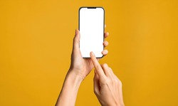 Close up of woman hand using smartphone isolated on orange wall. Female hands showing empty white screen of modern smart phone. Businesswoman holding cellphone and unlocks it with her fingerprint.