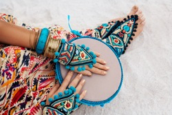 close up of woman hands and legs in ethnic jewelry with drum