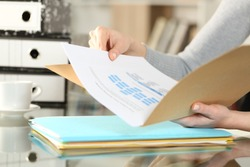 Close up of woman hands checking documents on folders sitting on a desk at home