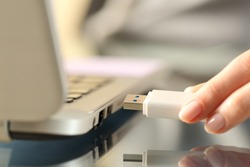 Close up of woman hands connecting usb flash drive on a laptop computer