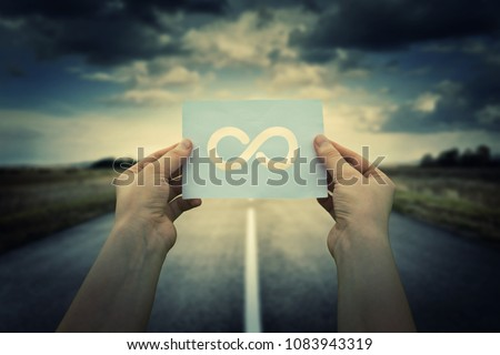 Close up of woman hands holding a paper sheet with infinite sign inside, over endless asphalt road background. The infinity way to nowhere, business confusion concept.